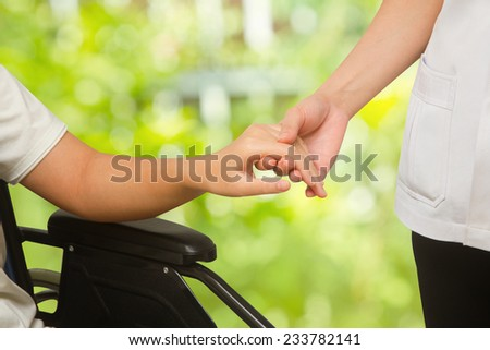 Doctor supporting  patient in wheelchair  on green background - stock photo