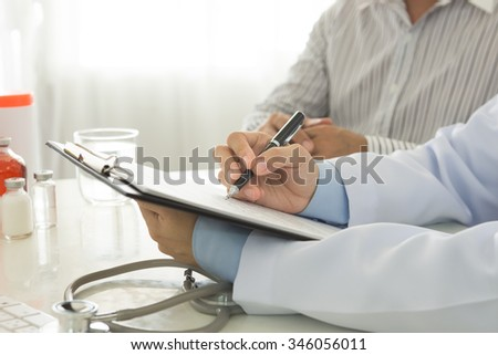 doctor take notes with patient in hospital.  healthcare and medical concept. - stock photo