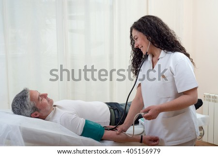 doctor takes the pressure blood to patient stretched in stretcher - stock photo