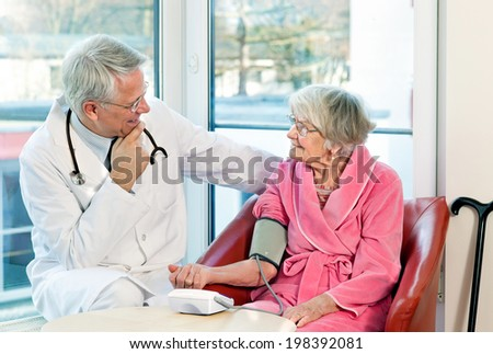 Doctor taking an elderly womans blood pressure with a sphygmomanometer or pressure cuff as they sit talking during a consultation in the clinic - stock photo
