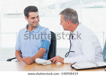 Doctor taking blood pressure of smiling patient in bright surgery