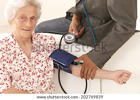 Doctor taking blood pressure to patient at home looking at camera - stock photo