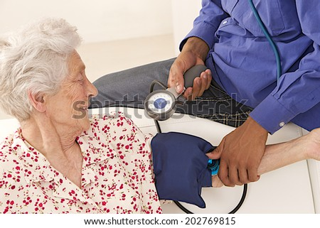Doctor taking blood pressure to  smiling patient at home  - stock photo