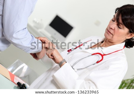 Doctor taking her patient's pulse - stock photo