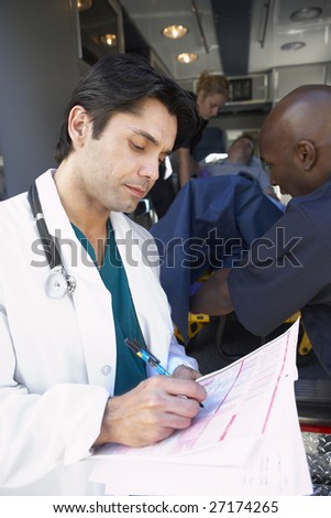 Doctor taking notes as paramedics unload patient - stock photo