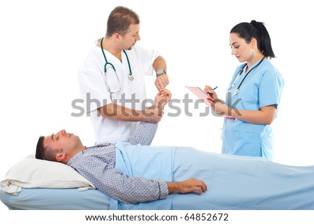 Doctor taking patient sleeping man pulse while a nurse writing in clipboard in hospital