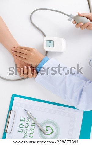 Doctor taking pulse of the patient who has life insurance policy, view from the top - stock photo