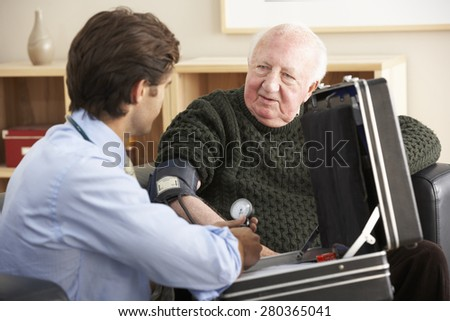Doctor taking senior man's blood pressure at home - stock photo
