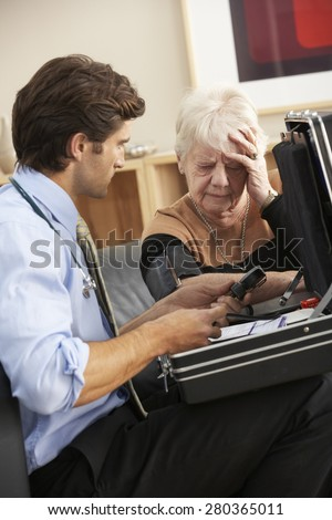 Doctor taking senior woman's blood pressure at home - stock photo