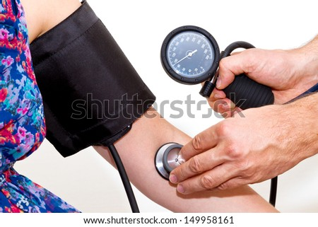 Doctor taking young woman�´s blood pressure - stock photo