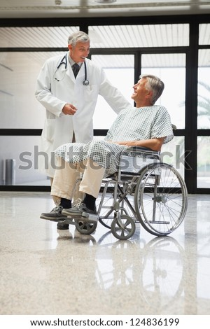 Doctor talking to a man  in a wheelchair smiling  in hospital corridor - stock photo