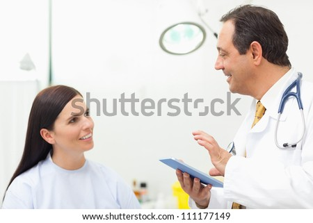 Doctor talking to a patient while holding a tablet tactile in an examination room - stock photo