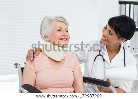 Doctor talking to a senior patient with cervical collar at the hospital - stock photo