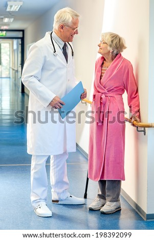 Doctor talking to an elderly woman patient dressed in a pink dressing gown and holding a walking stick in the corridor of the hospital with a file in his hands.