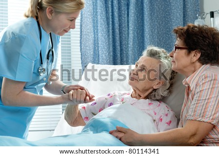 Doctor talking to elderly patient lying in bed in hospital - stock photo