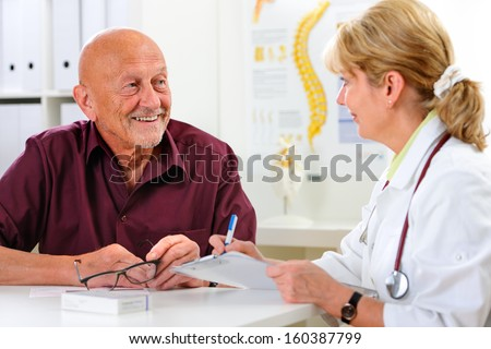 Doctor talking to her male senior patient at the office - stock photo