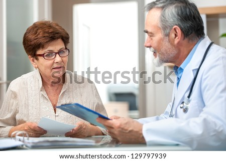 doctor talking to his female patient at office - stock photo