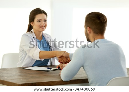 Doctor talking to male patient in room on light background