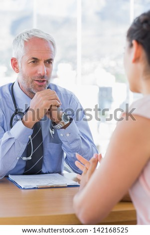Doctor talking to patient in his office - stock photo