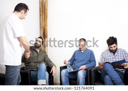 Doctor talking to patient in waiting room - stock photo