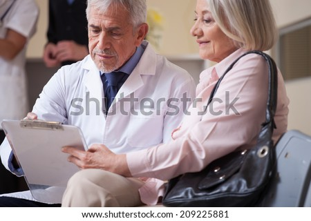 Doctor talking to patient in waiting room. - stock photo