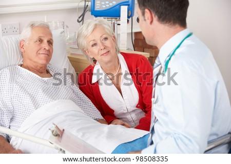 Doctor talking to senior couple on UK Hospital ward - stock photo
