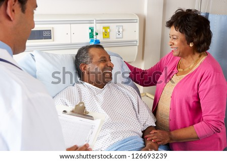 Doctor Talking To Senior Couple On Ward - stock photo