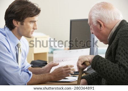 Doctor talking to senior male patient - stock photo