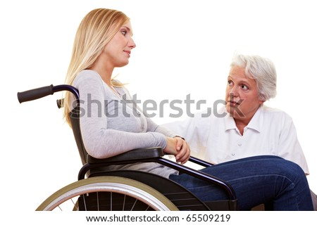 Doctor talking to young disabled woman in wheelchair