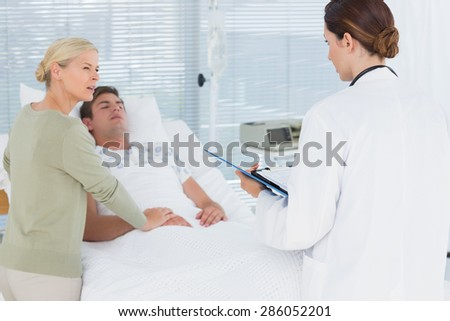 Doctor talking with her patients mother in hospital room - stock photo