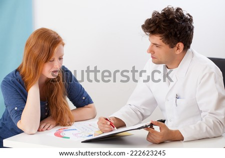 Doctor talking with young patient and his office - stock photo