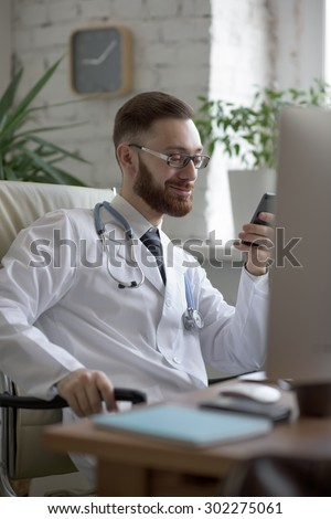 Doctor texting on his smartphone - stock photo