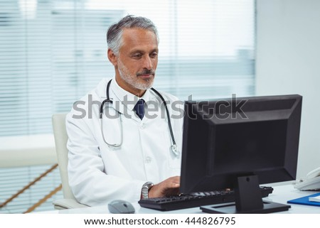 Doctor typing on his computer in cabin - stock photo