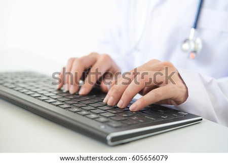 Doctor typing on keyboard and using smart phone. doctor appointment concept.