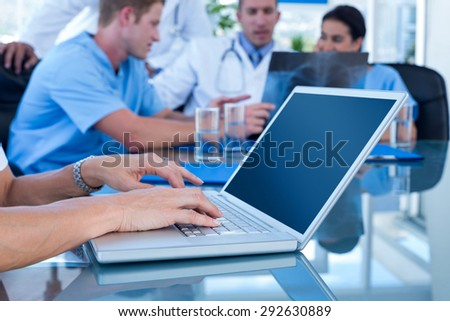Doctor typing on keyboard with her team behind in medical office - stock photo