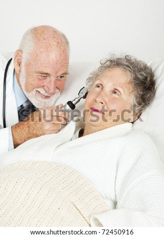 Doctor uses an otoscope to check inside his senior patient's ears. - stock photo