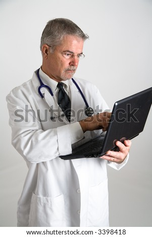 Doctor using a laptop computer - stock photo