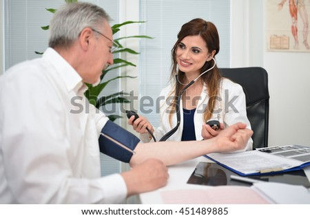 Doctor using a stethoscope and a sphygmomanometer to check blood pressure - stock photo