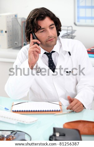 Doctor using a telephone at a desk - stock photo