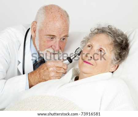 Doctor using an otoscope to examine a hospital patient's ear canal. - stock photo