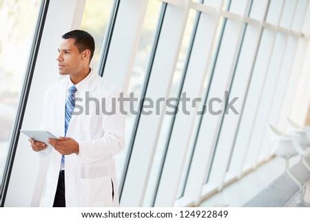 Doctor Using Digital Tablet In Corridor Of Modern Hospital - stock photo