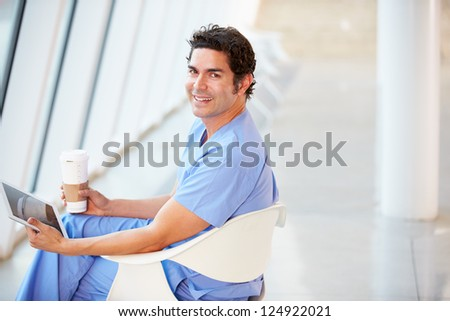Doctor Using Digital Tablet On Coffee Break In Hospital - stock photo