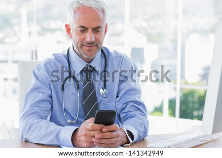 Doctor using his smartphone in the office at desk - stock photo