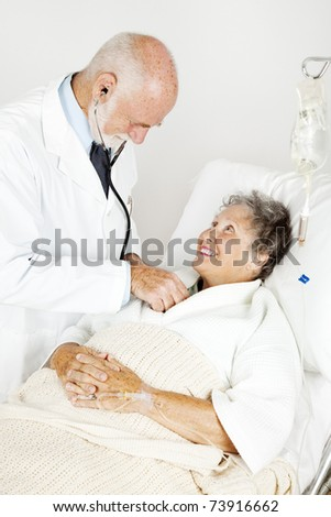 Doctor using his stethoscope to listen to an elderly hospital patient's heart. - stock photo