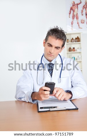 Doctor using mobile phone, sitting at desk . - stock photo