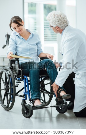 Doctor visiting an invalid woman in wheelchair, he is examining her leg, rehabilitation and physioteraphy concept - stock photo