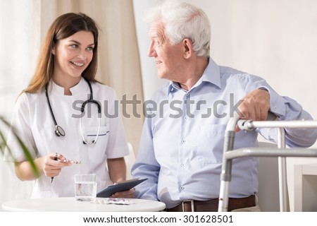 Doctor visiting disabled senior patient at home - stock photo