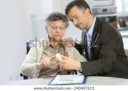Doctor visiting elderly patient at home  - stock photo