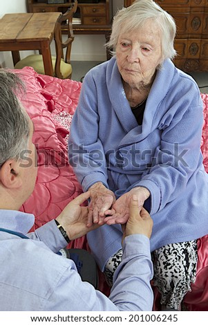Doctor visiting elderly patient at home, hand examination - stock photo