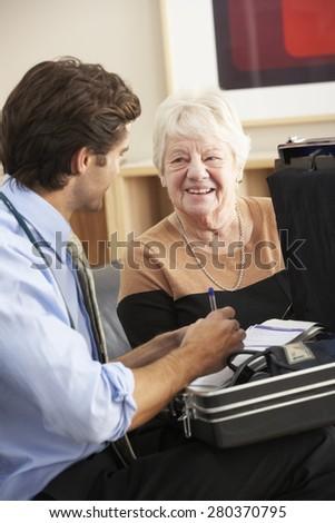 Doctor visiting senior woman at home - stock photo